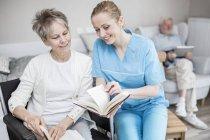 Cuidador livro de leitura com a mulher idosa com o homem sênior usando tablet em segundo plano em casa de cuidados . — Fotografia de Stock