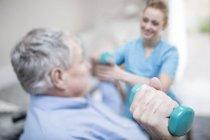 Fisioterapeuta ayudando al hombre mayor a levantar pesas de las manos . - foto de stock