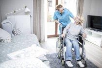 Senior femme en fauteuil roulant, parler avec l'éducateur en foyer de soins. — Photo de stock
