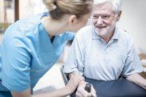 Travailleur des services féminins aidant à homme senior à l'aide de déambulateur en foyer de soins. — Photo de stock