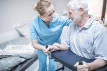 Senior homme avec déambulateur infirmière aidant. — Photo de stock