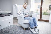 Старший женщина, сидя в кресле с журналом в домашний уход. — стоковое фото