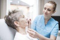 Feminina enfermeira inserir a cânula nasal em mulher sênior — Fotografia de Stock