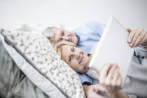 Senior couple lying down in bed and watching digital tablet. — Stock Photo