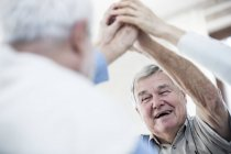 Senior men giving high five, low angle view. — Stock Photo