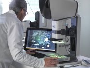 Engineer using stereo microscope for inspecting printed circuit board during quality control process. — Stock Photo