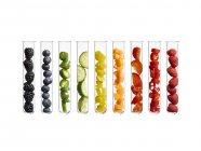 Frutas y verduras coloridas en tubos de ensayo, toma de estudio . - foto de stock