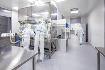 Techniciens qui travaillent dans le laboratoire biomédical stérile et scellé. — Photo de stock