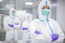 Lab technician in protective clothing with colleagues in sterile laboratory environment. — Stock Photo