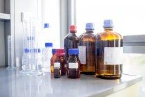Solutions de laboratoire et verrerie sur table . — Photo de stock