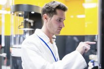 Male technician programming electrospinning machine in nanofibre laboratory. — Stock Photo