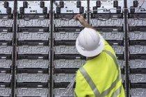 Ingeniero que conecta las baterías de almacenamiento de energía para la energía de reserva a la central eléctrica . - foto de stock