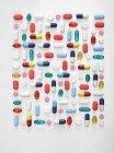 Colocación plana de píldoras y cápsulas surtidos contra fondo blanco . - foto de stock