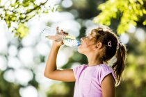 Side view of girl drinking water from plastic bottle in park. — Stock Photo