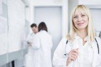 Ritratto di medico femminile che sorride a porte chiuse con i colleghi nella priorità bassa. — Foto stock