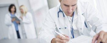 Mitte erwachsener männlicher Arzt macht Papierkram mit Kollegen im Hintergrund. — Stockfoto
