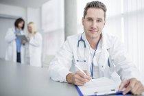 Mitte erwachsener männlicher Arzt macht Papierkram und schaut in die Kamera. — Stockfoto