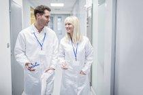 Medici maschii e femminili in camice bianco che cammina giù il corridoio. — Foto stock
