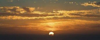 Dramatique ciel coucher de soleil rougeoyant orange, avec des nuages. — Photo de stock