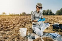 Agronomista abertura saco de amostra de solo no campo . — Fotografia de Stock