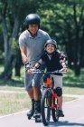Abuelo y nieto cabalgando juntos en patines y bicicleta en el parque. - foto de stock