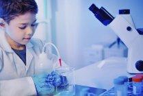 Écolier utilisant la verrerie et l'équipement dans le laboratoire de l'école . — Photo de stock