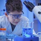 Schoolboy using glassware and equipment in school laboratory. — Stock Photo