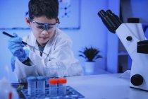 Écolier faisant des expériences scientifiques dans un laboratoire de chimie scolaire . — Photo de stock