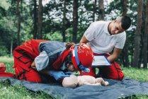 Женщина-парамедик с инструктором по искусственному дыханию на открытом воздухе . — стоковое фото