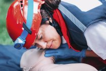 Female paramedic practicing mouth-to-mouth while CPR training outdoors. — Stock Photo