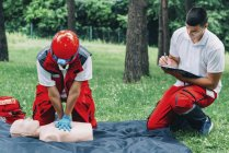 Woman with paramedic instructor CPR training on dummy outdoors. — Stock Photo