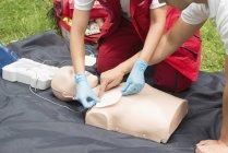 Instructor helping female paramedic using defibrillator training outdoors. — Stock Photo
