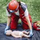 Female paramedic CPR training on baby dummy outdoors. — Stock Photo