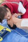 Женщина-парамедик практикует кардиолегочную реанимацию на манекене . — стоковое фото