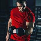 Молодой человек тренируется с гантелями в тренажерном зале . — стоковое фото