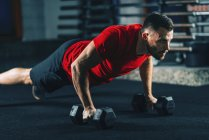 Young man exercising with dumbbells in gym. — Stock Photo