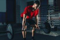Мускулистый мужчина в красной футболке, поднимающий тяжести в спортзале . — стоковое фото