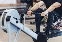 Cropped view of man in rowing machine workout. — Stock Photo