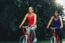 Deux femmes adultes moyennes faisant le vélo ensemble en stationnement. — Photo de stock