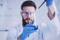 Молодой ученый-мужчина, работающий в лаборатории со стеклом . — стоковое фото