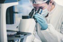 Microbiologiste inspectant la croissance des bactéries au microscope optique . — Photo de stock