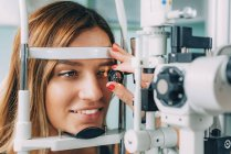 Ophthalmologist examining patient with slit lamp and magnifying lens. — Stock Photo