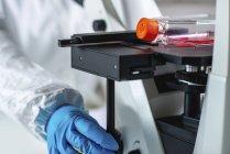 Ingénieur en biotechnologie inspectant la fiole de culture cellulaire . — Photo de stock