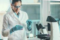Forscherin mit Mikropipette im Reagenzglas. — Stockfoto
