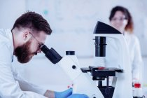 Jeune chercheur masculin regardant un échantillon au microscope . — Photo de stock