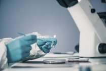 Microbiologiste travaillant en laboratoire avec la croissance des bactéries dans la boîte de Pétri . — Photo de stock
