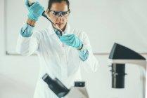 Chercheuse scientifique travaillant en laboratoire et pipettant dans une éprouvette . — Photo de stock
