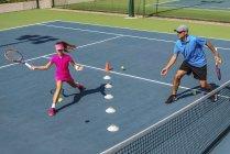 Adolescente tennista formazione con allenatore di sesso maschile sul campo da tennis . — Foto stock