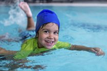 Smiling little boy learning swimming in swimming pool. — Stock Photo
