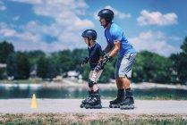 Старший преподаватель роликового спорта с мальчиком, практикующим на занятиях в парке . — стоковое фото